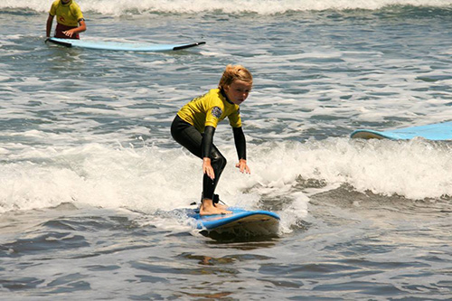 Un alumno de la escuela de surf coge una ola