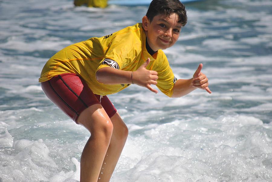 Un alumno de la escuela de surf hace un saludo surfero