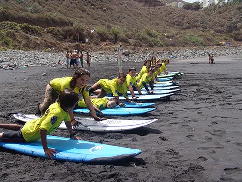 Practicando sobre la arena la técnica de puesta en pie en nuestra escuela de surf